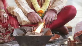 La mujer local del primer lanza las semillas sobre el fuego durante la purificación