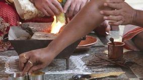 La mujer local del primer pone bolas ardientes en el pote de la chimenea
