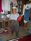 La mujer local del pueblo muestra las muñecas de la tela que él vende Imagen de archivo libre de regalías