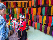 La mujer local se vistió en ropa tradicional delante de la lana de alpaca teñida en Awana Kancha foto de archivo