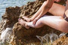 La mujer lubrica la protección solar de la piel imágenes de archivo libres de regalías