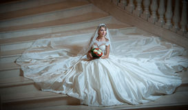 La mujer lujosa hermosa joven en el vestido de boda que se sienta en la escalera camina en semi-oscuridad Novia con el vestido de Foto de archivo libre de regalías