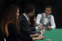La mujer más afortunada en el fondo de los jugadores en el casino fotos de archivo