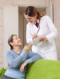 La mujer madura alegre dice a doctor los síntomas foto de archivo