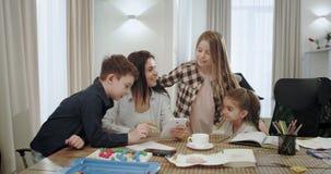 La mujer madura atractiva con sus tres niños pide algo en línea para sus niños que son muy felices abrazando cada uno almacen de metraje de vídeo