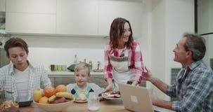 La mujer madura atractiva trae la comida por la mañana para sus miembros de la familia mientras que ellos que esperan en la tabla metrajes