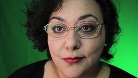 La mujer madura de Latina pone los vidrios con el fondo verde almacen de video