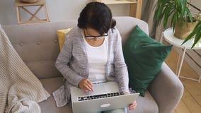 La mujer madura en rebeca gris se está sentando en el sofá almacen de video