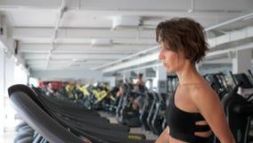 La mujer madura está entrenando en la rueda de ardilla en gimnasio Aptitud, concepto del deporte almacen de metraje de vídeo