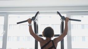 La mujer madura está haciendo tirón-UPS con el apretón ancho en el gimnasio, visión trasera almacen de video