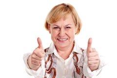 La mujer madura feliz que muestra los pulgares sube la muestra Imágenes de archivo libres de regalías