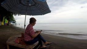 La mujer madura hojea Internet con el uso del smartphone móvil mientras que sienta la sombrilla inferior legged cruzada del paras