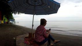 La mujer madura hojea Internet con el uso del smartphone móvil mientras que sienta la sombrilla inferior legged cruzada del paras metrajes