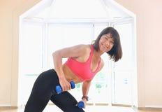 La mujer madura levanta pesos en el gimnasio Imagen de archivo