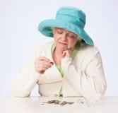 La mujer madura pobre mira la moneda y piensa con la mano debajo de Chin Foto de archivo