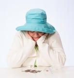 La mujer madura pobre mira monedas con ambas manos que ahueca a Chin Imágenes de archivo libres de regalías