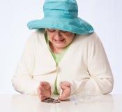 La mujer madura pobre mira monedas en la tabla Fotos de archivo