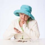 La mujer madura pobre piensa en monedas a disposición Foto de archivo libre de regalías