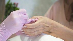 La mujer madura se está sentando en el nailsalon y está recibiendo la manicura rosada hermosa del gel almacen de metraje de vídeo
