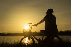 La mujer madura se sienta en la bicicleta retra del vintage cerca del lago en el momento de la puesta del sol siluetee la bicicle Imagenes de archivo
