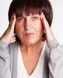 La mujer madura tiene un dolor de cabeza fotos de archivo libres de regalías