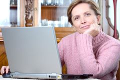 La mujer madura trabaja en la computadora portátil imagenes de archivo