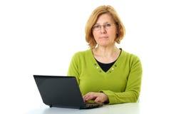La mujer madura trabaja en su computadora portátil, aislada Foto de archivo libre de regalías