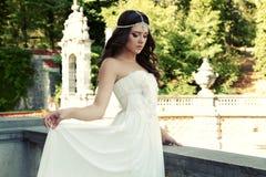 La mujer magnífica con el pelo oscuro lleva el vestido y la joya lujosos Imagen de archivo libre de regalías