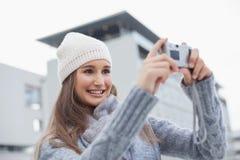 La mujer magnífica sonriente con invierno viste en tomar una imagen del uno mismo Foto de archivo libre de regalías