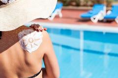 La mujer magn?fica tiene un sol form? el sunblock en su hombro por la piscina Factor de protecci?n de Sun en las vacaciones, conc fotos de archivo libres de regalías