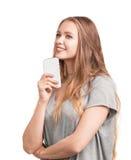 La mujer magnífica y joven con los ojos azules claros y el pelo recto largo sostiene un teléfono elegante, aislado en un fondo bl Imagen de archivo