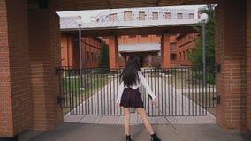 La mujer malasia se opone con su parte posterior a la cerca con el arma fría del katana almacen de metraje de vídeo