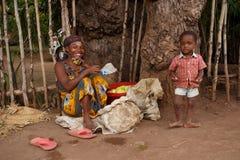La mujer malgache con el niño que vende las frutas, entrometidas sea puerto, Madagasc Foto de archivo libre de regalías