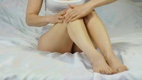 La mujer mancha la crema en sus piernas concepto del cuidado de pie, prevención de varices Cámara lenta almacen de metraje de vídeo
