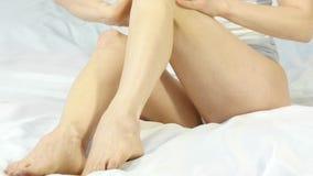 La mujer mancha la crema en sus piernas concepto del cuidado de pie, prevención de varices 4K almacen de video