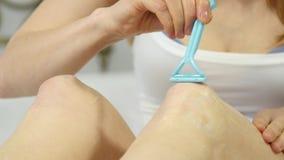 La mujer mancha la crema en sus piernas concepto del cuidado de pie, prevención de varices 4K almacen de metraje de vídeo