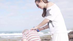 La mujer mancha el cuello del niño con crema de la protección del sol almacen de metraje de vídeo