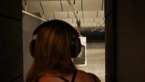 La mujer manipula una blanco en un resbalador motorizado en una gama de leña del arma metrajes