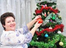 La mujer mayor adorna el árbol de navidad Imagen de archivo
