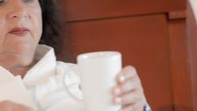 La mujer mayor adulta en una albornoz blanca que miente en una cama en un hotel toma un vaso de agua de una mesita de noche y de  almacen de metraje de vídeo