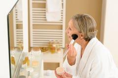 La mujer mayor aplica el polvo del maquillaje en cuarto de baño imagen de archivo