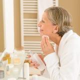 La mujer mayor aplica la loción de la limpieza de la cara Fotos de archivo libres de regalías