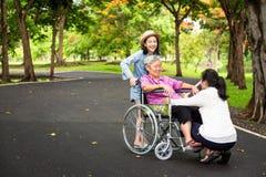 La mujer mayor asiática en silla de ruedas con poca muchacha del niño que apoya, goza en caminar la naturaleza verde, abuela con  imagen de archivo libre de regalías