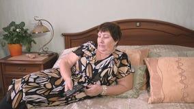 La mujer mayor cambia el telecontrol de los canales TV almacen de metraje de vídeo