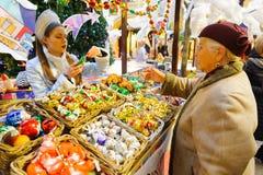 La mujer mayor compra el juguete de la Navidad en el Año Nuevo justo Imagen de archivo