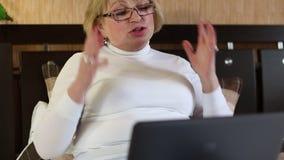 La mujer mayor comunica con el ordenador portátil Mujer con el cuaderno almacen de metraje de vídeo