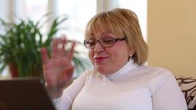 La mujer mayor comunica con el ordenador portátil Mujer con el cuaderno metrajes