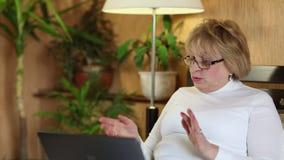 La mujer mayor comunica con el ordenador portátil Mujer con la computadora portátil almacen de video