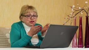 La mujer mayor comunica el ordenador portátil de las aplicaciones Mujer con la computadora portátil metrajes