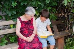 La mujer mayor con el grande-nieto leyó el libro Fotografía de archivo libre de regalías